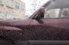 Wet car window with raindrops and a blurred car Royalty Free Stock Photography