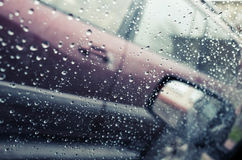 Wet car window with raindrops and a mirror behind Royalty Free Stock Photography
