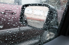 Wet car window with raindrops and a mirror behind Stock Photos