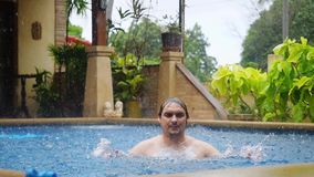Wet caucasian man gets rained enjoyes while swimming in pool splashing water on vacation. 1920x1080. Wet caucasian man gets rained enjoyes while swimming in pool stock video footage