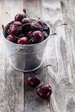 Wet Cherries in a Bucket on a Wooden Table Royalty Free Stock Photo