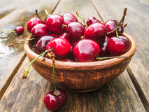 Wet cherries in an earthenware bowl. On an old country table after rain Royalty Free Stock Photo