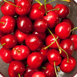 Wet cherries in stainer Stock Photos