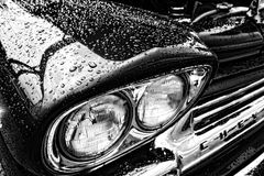 Water Drops on Classic Vintage Chevrolet Fender. Water drops and rain droplet on classic vintage Chevrolet automobile wet fender with retro headlight detail Royalty Free Stock Image