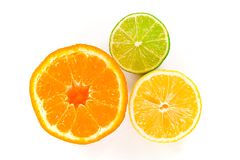 Wet Citrus Trifecta. Half a wet orange, lemon and lime closeup, isolated against a white background Royalty Free Stock Photo