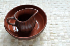 Wet clay pot in basin. A wet clay pot rests in a wet clay basin Stock Photo