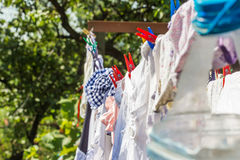 Wet clothes with clothespins on the rope. At outdoors royalty free stock image