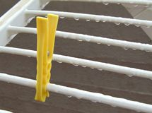 Wet dryer with one bright clothes peg. Wet clothes dryer with raindrops with one bright clothes peg. foto can be used to advertise a tumble dryer. Situation royalty free stock images