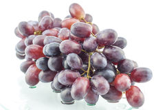 Wet cluster of grapes on a glass table Stock Images