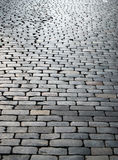 Wet cobbles of block pavement. Rough texture of wet block pavement, chains of chaps running away Stock Photo