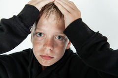 Wet and cold boy with hands on head. Close up on single wet and cold blond boy wearing black coat with hands on top of his head over gray background Stock Photo