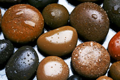 Wet colored stones background, dark pebbles with water drops Royalty Free Stock Photography