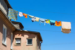 Wet colorful clothing is hanging on the cord. Old district of Klaipeda Stock Images