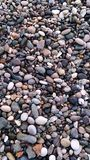 Wet colorfull sea pebbles on the beach stock images