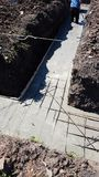Wet concrete is poured on wire mesh steel reinforcement Stock Photo