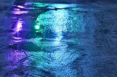 Wet concrete sidewalk after rain, colorful lights