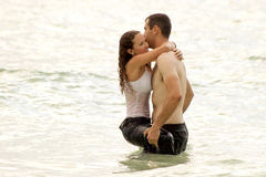 Wet couple hugging in the ocean. A bare chested young man is holding a soaking wet woman in the water, she is smiling, fully clothed and hugging him Stock Image
