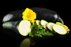 Wet courgettes cut into slices with flower and leaf on black. Mature wet courgettes cut into slices with flower and courgette leaf on black background Royalty Free Stock Photo