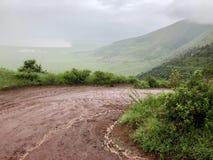 Wet curvy Seneto Descent road, descending into the foggy rainy Ngorongoro crater in Tanzania, Africa. Wet curvy Seneto Descent road, descending into the foggy stock photo