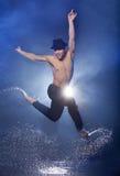 Wet dancer. Young male dancer in black fedora dancing on the wet floor Royalty Free Stock Photo