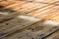 Wet deck boards surface with raindrops in a sunlight Royalty Free Stock Photo