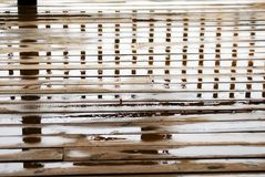 Wet Deck Reflections. A wet wooden deck with reflections of the railing royalty free stock photos