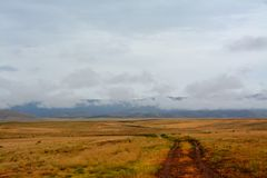 A wet dirt road leads into the Prescott Valley Landscape. A dirt road leads into the Prescott Valley golden landscape in Arizona, wet from a recent rain Royalty Free Stock Photography