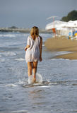 Wet dress. The girl in a wet shirt and the man at coastline Royalty Free Stock Photo
