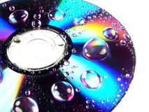 Wet DVD Rainbow. A wet dvd disc with rainbows and reflections amidst the water drops Stock Image