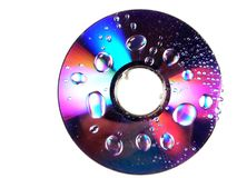 Wet DVD Rainbow. A wet dvd disc with rainbows and reflections amidst the water drops Stock Photography