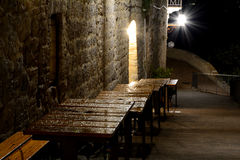 Wet, empty, wooden restaurant tables at night Royalty Free Stock Images