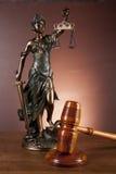 Wet en rechtvaardigheidsmateriaal op houten lijst, donkere achtergrond Stock Afbeeldingen