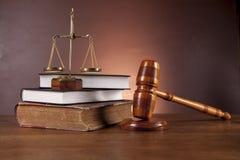 Wet en rechtvaardigheidsmateriaal op houten lijst, donkere achtergrond Stock Foto