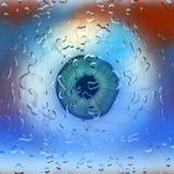Wet eyeball. Closeup of eye ball behind wet glass Royalty Free Stock Images