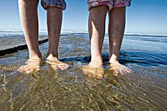 Wet feet. Two kids with bare feet in the water Stock Images