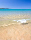 Wet Feet. A crystal clear wave meanders over golden sand at palm beach Royalty Free Stock Photo