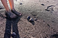 Wet feet on black beach sand. Wet grit covered feet standing on black sandy beach Royalty Free Stock Images