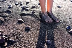 Wet feet on black sandy beach. Royalty Free Stock Images