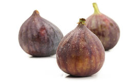 Wet fig in front of two figs Royalty Free Stock Photo