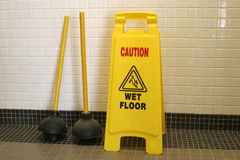 Wet floor. A wet floor sign sitting in a bathroom with two plungers Stock Photo