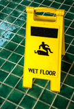 Wet floor caution sign. With rain drop on the green tiles floor royalty free stock images