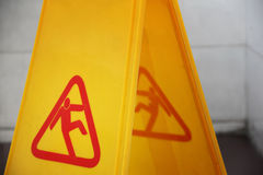 Wet floor sign closeup. Close up of yellow wet floor sign in a dark bathroom interior Royalty Free Stock Photos