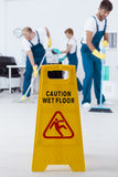 Wet floor sign. And group of busy young cleaners working Stock Photography