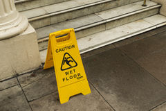 Wet floor sign in London. Yellow wet floor sign in London Stock Photos