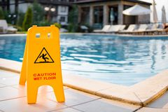 Wet floor sign by luxury swimming pool. Wet floor sign by luxury hotel swimming pool Stock Images