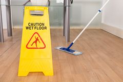 Wet floor sign and mop. Close-up Of Wet Floor Sign And Mop On Hardwood Floor Royalty Free Stock Image