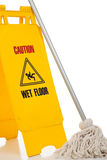 Wet floor sign and mop on white background. A wet floor sign and mop on a white background Royalty Free Stock Images