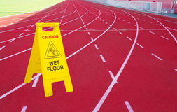 Wet floor sign and running track Royalty Free Stock Photography