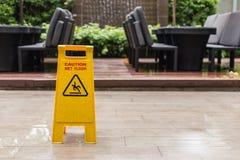 Wet floor warning sign on the floor in hotel corridor. Yellow wet floor warning sign on the floor in hotel corridor Stock Images