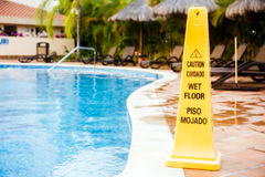 Wet floor warning. Sign on a swimming pool in Mexico Royalty Free Stock Images